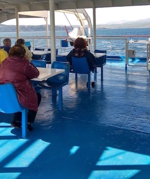 Passengers relaxing on deck of boat heading to Skopelos Island